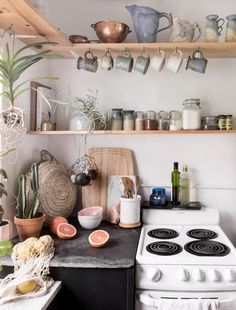 Homey kitchen with a DIY rustic feel. Open shelves, jars, plants, small kitchen